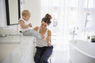 Mother tickling toes of baby daughter in bathroom - HEROF10171
