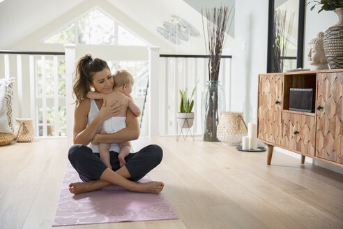 Affectionate mother holding baby daughter on yoga mat - HEROF10183