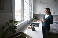 Smiling woman drinking coffee and looking out kitchen window - HEROF10266