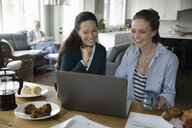 Mother and adult daughter using laptop at dining table - HEROF10269
