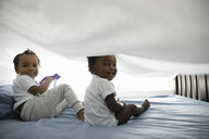 Portrait playful toddler brothers playing underneath sheet on bed - HEROF10275