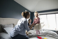 Happy parents and toddler daughter playing on bed - HEROF10302