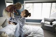 Affectionate, playful mother lifting daughter on bed - HEROF10305