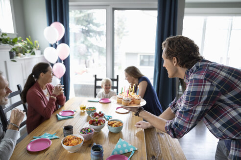 Multi-generation family celebrating toddler girl s birthday with cupcakes at dining table - HEROF10317