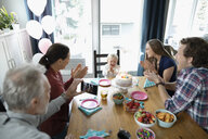 Multi-generation family celebrating toddler girl s birthday at dining table - HEROF10320