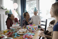Multi-generation family celebrating toddler girl s birthday at dining table - HEROF10329