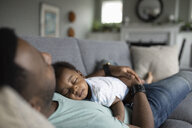 Tired baby son sleeping on father on living room sofa - HEROF10341