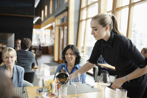 Waitress pouring water for businesswoman at restaurant table - HEROF10374