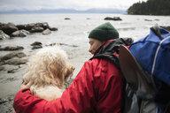 Man and dog backpacking on rugged beach - HEROF10388