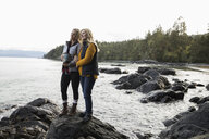 Mother and daughter with urn spreading ashes on rugged beach - HEROF10406