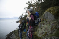 Mother and daughter backpacking on cliff overlooking ocean - HEROF10412