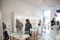 Jewelry boutique owner helping woman shopping for jewelry at display case - HEROF10421