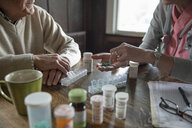 Home caregiver organizing medication in pill boxes for senior man - HEROF10433