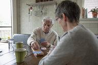 Home caregiver and senior man playing cribbage at kitchen table - HEROF10439