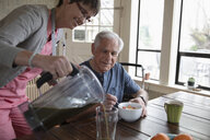 Home caregiver pouring green smoothie for senior man at kitchen table - HEROF10442