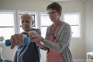 Home caregiver helping senior man exercising, weightlifting with dumbbells - HEROF10445