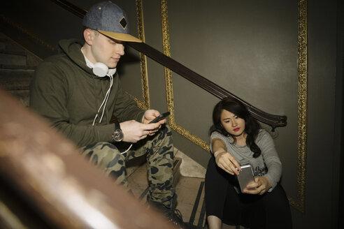 Millennial friends using smart phones on nightclub stairs - HEROF10508