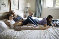 Mother and daughters relaxing, watching TV on bed - HEROF10523