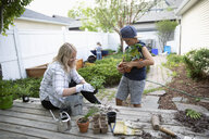 Mother and son potting plants on deck - HEROF10580