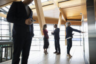 Business people talking in office corridor - HEROF10617