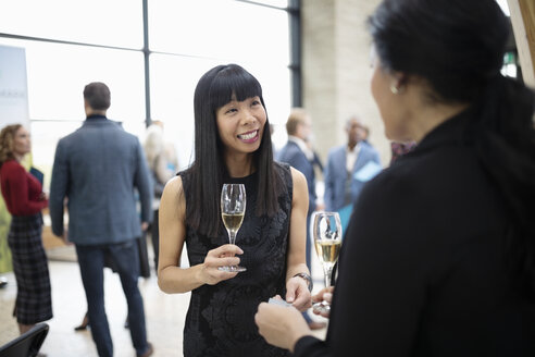 Smiling businesswomen networking, drinking champagne at conference happy hour - HEROF10647