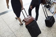 Business people pulling suitcases in airport - HEROF10692