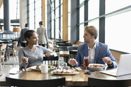Business people working and eating lunch in restaurant - HEROF10725