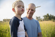 Portrait father holding son chewing on wheat stalk in rural field - HEROF10761