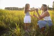 Mother and daughter in sunny, rural field - HEROF10770