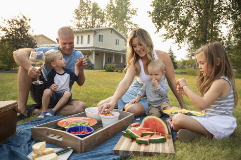 Young family enjoying picnic in rural yard - HEROF10773