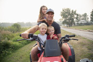 Father and young children riding quadbike on farm - HEROF10779