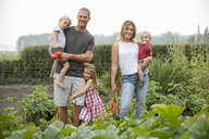 Portrait happy young family harvesting fresh vegetables in rural vegetable garden - HEROF10797