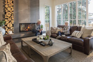 Senior couple relaxing, drinking wine and talking in living room - HEROF10812