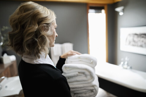 Female room service hotel staff with towels in luxury bathroom - HEROF10917