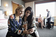Smiling women friends using smart phone and drinking champagne, enjoying spa weekend in hotel room - HEROF10935