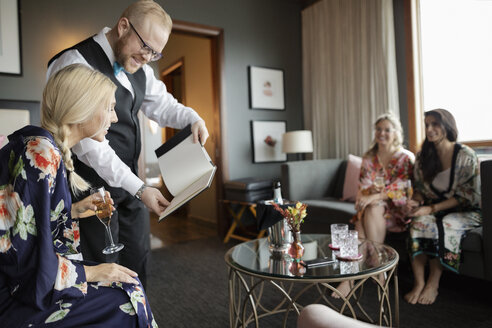 Room service hotel staff waiter showing menu to woman drinking champagne in hotel room - HEROF10938