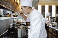 Chef tasting sauce at stove in restaurant kitchen - HEROF10971