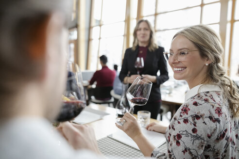 Smiling woman drinking red wine in restaurant - HEROF10989