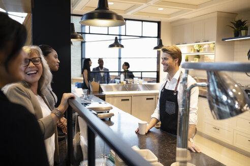 Cafe worker helping businesswomen - HEROF11034