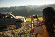 Woman with digital camera photographing sunny mountain view behind SUV, Alberta, Canada - HEROF11064