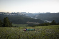 Woman camping, sleeping in tent in mountain field, Alberta, Canada - HEROF11067