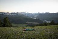 Woman camping, sleeping in tent in mountain field, Alberta, Canada - HEROF11067