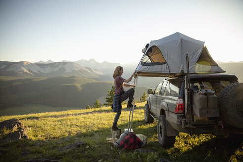 Woman camping, climbing up to SUV rooftop tent in idyllic mountain field, Alberta, Canada - HEROF11070