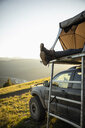 Womans feet dangling from SUV rooftop tent in idyllic mountain field, Alberta, Canada - HEROF11073