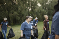Woman with down syndrome volunteering, cleaning up garbage in park - HEROF11112