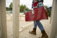 Woman carrying toolbox at construction site - HEROF11115