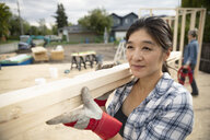 Woman carrying wood planks at construction site - HEROF11118