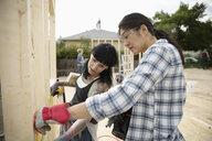 Women measuring frame, helping build house - HEROF11136