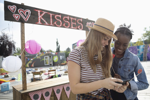 Young women with smart phone at kissing booth - HEROF11157