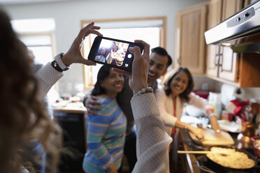 Woman with camera phone photographing family cooking in kitchen - HEROF11229